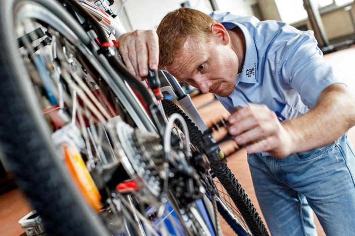 Businessfotografie Mitarbeiter in der Fahrradwerkstatt
